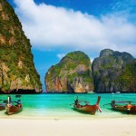 Thailand tropical beach, traditional long tail boats, famous Maya Bay